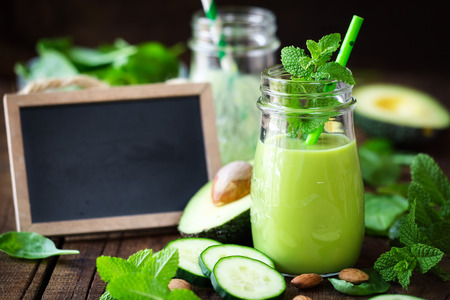 Green detox smoothie with avocado, cucumber, spinach and with fresh mint. Healthy eating, weight loss and dieting concept with a blackboard at the backgrond with copy space for your text