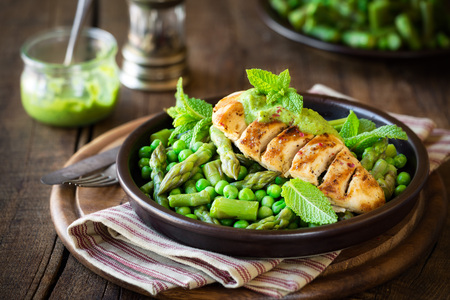 Delicious healthy homemade dinner with grilled chicken breast garnished with green peas, asparagus stalks and mint sauce against dark rustic background