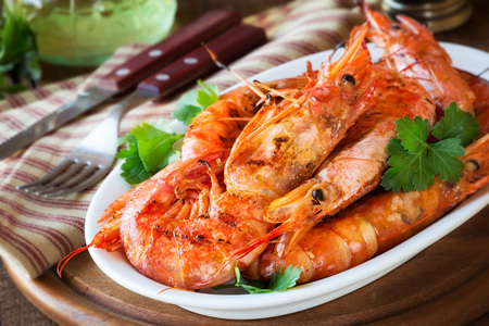 Griller King prawns or shrimps with parsley on white plate on dark rustic wooden table Lizenzfreie Bilder