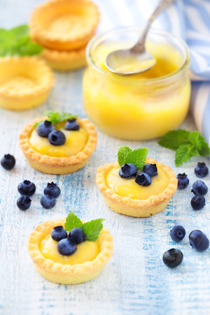 Mini tarts filled with lemon curd or custard and decorated with fresh blueberries and mint