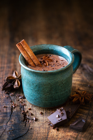Cup of hotchocolate with a cinnamon stick, star anise and grated dark chocolate as a topping on dark rustic wooden background