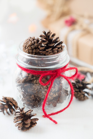 White Christmas setting. Pine cones in a glass jar decorated with a red festive twine and wrapped gifts at the background