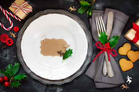 Christmas table setting with a vintage plate, silverware wrapped in a napkin surrounded by xmas gifts, gingerbread cookies, holly leaves and festive ornaments Standard-Bild