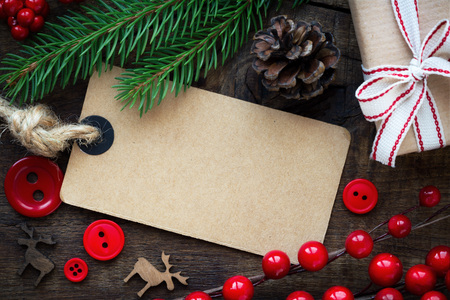 Kraft paper empty tag with Christmas ornaments and gifts on dark rustic wooden background. Overhead view Standard-Bild