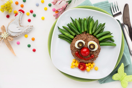 Fun food for kids - cute smilig clown face on a meat hamburger or ground meat pattie with green beans for a healthy dinner for children. Creative cooking idea Standard-Bild