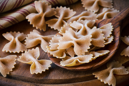 Wholemeal or whole grain farfalle pasta closeup
