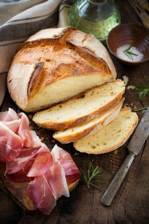 Freshly baked homemade bread on dark rustic wooden table with sliced prosciutto ham, salt and olive oil at the background Standard-Bild