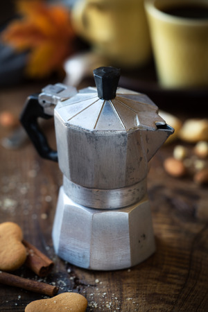 Good morning concept - traditional Italian old moka pot on dark rustic wooden table with two cups of coffee at the background Stock Photo