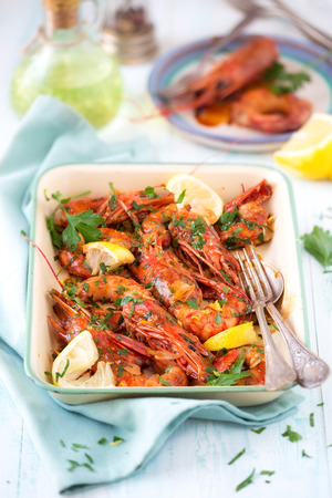 Giant prawns sauteed with garlic, parsley and lemon with honey glaze on a vintage cooking tray