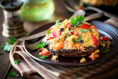 Stuffed mushroom - delicious vegan couscous stuffed Portobello mushroom served on a dark plate