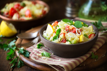 Vegetarian tabbouleh - delicious couscous salad with cherry tomatoes, cucumbers, fresh mint and parsley leaves.