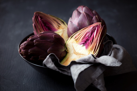 Fresh ripe artichokes in a bowl against black wooden background 版權商用圖片