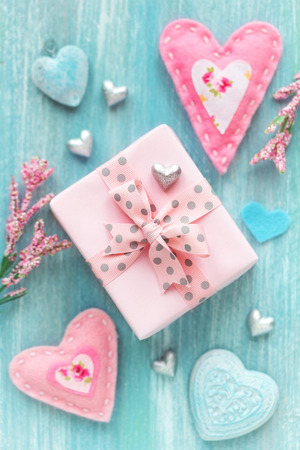 Valentines Day concept with twrapped gift box and many different hearts on turquoise color wooden background