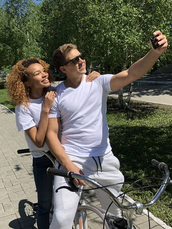 young beautiful loving couple caring girlfriend and boyfriend taking a selfie on a bike