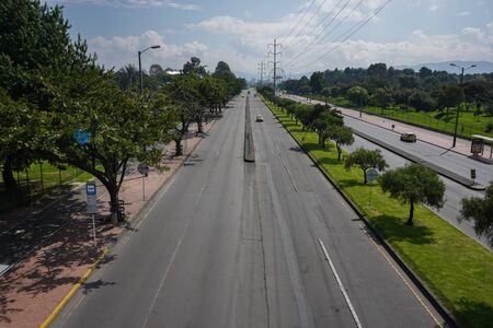 Aerial view of a street without cars or people in summer with many trees and white clouds