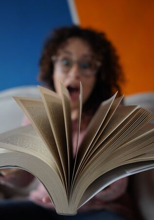 surprised woman with glasses and curly hair looking through the moving pages of an open book