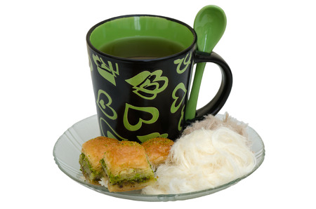 Baklava with pistachio, pismaniye and cup on a white background