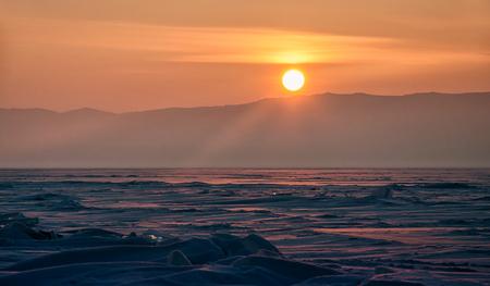 Field of ice hummocks on the frozen Lake Baikal. Sunset