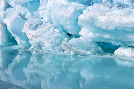 Blue growler piece of iceberg with reflection in calm water. Arctic ocean