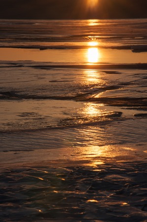 alone in the dark: Ice texture of a frozen lake Baikal in the winter in the sun at sunset