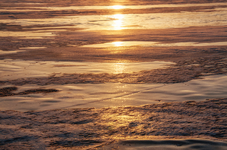 Ice texture of a frozen lake Baikal in the winter in the sun at sunset