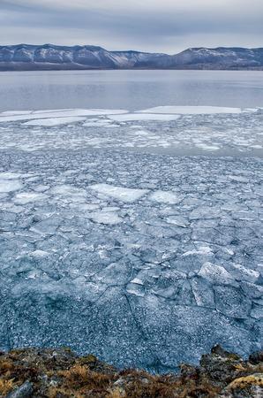 Baikal Lake e rock no frio de dezembro. Tempo de congelamento. Os floes de gelo estão nadando na água Foto de archivo - 89134020