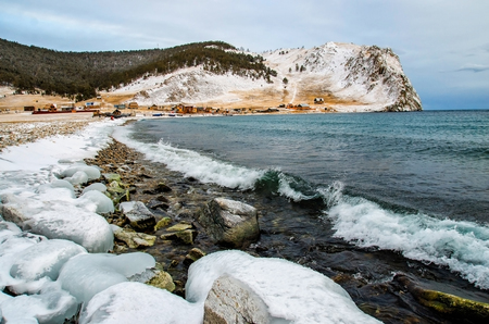 Waves and splash on Lake Baikal with rocks and trees near Uzuri village