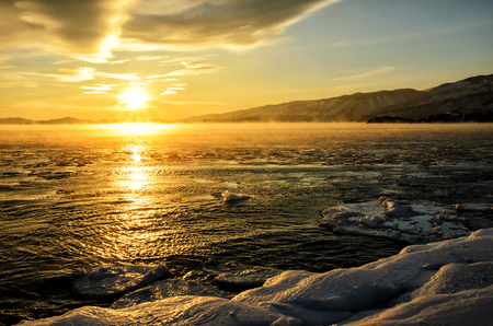Ice floes floating on the fog water in the lake Baikal. Sunset Standard-Bild
