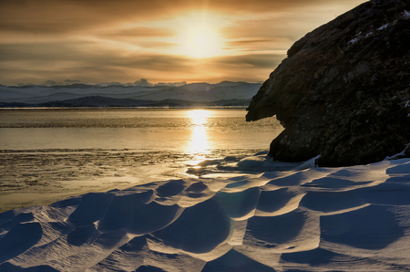 Winter sunset near the rocks with snow the frozen Baikal Lake