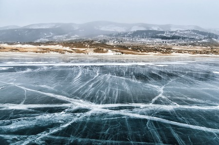 Frozen Lake Baikal. Beautiful mountain near the ice surface on a frosty day. Natural background