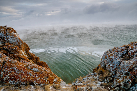 Baikal Lake and rock in the December cold. Time of freeze-up. Ice floes is swiming on the water Foto de archivo - 92557976