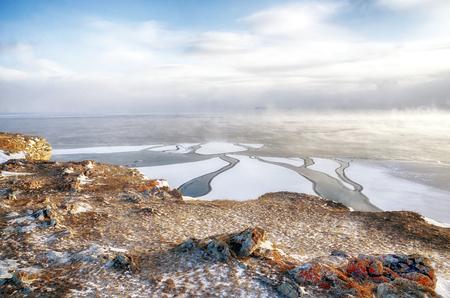 Lago Baikal y roca en el frío de diciembre. Tiempo de congelación Los témpanos de hielo están nadando en el agua Foto de archivo - 92939215