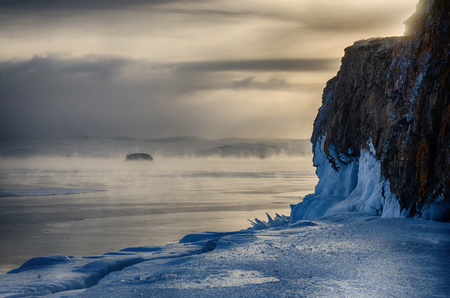 Field of ice hummocks and rock on the frozen Lake Baikal. Sunset. Russia