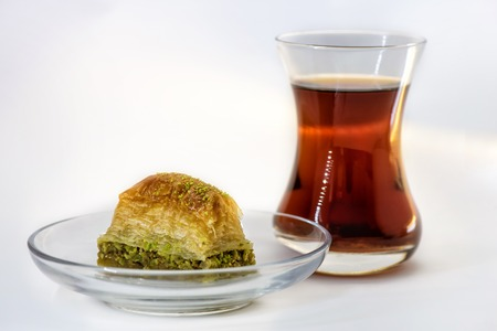 Baklava with pistachio and turkish cup of tea on a white background Stock Photo