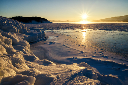 Ice floes floating on the fog water in the lake Baikal and hill. Sunset