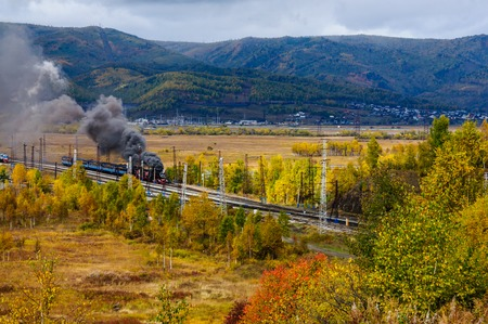 Old steam locomotive in the Circum-Baikal Railway with smoke in autumn 写真素材