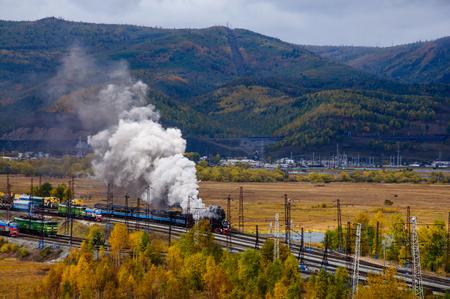 秋に煙が立つサーカムバイカル鉄道の古い蒸気機関車 写真素材
