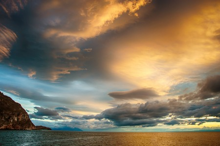 Sunset over stormy clouds across the water reflecting dark and looming dramatic sky moody Stock Photo