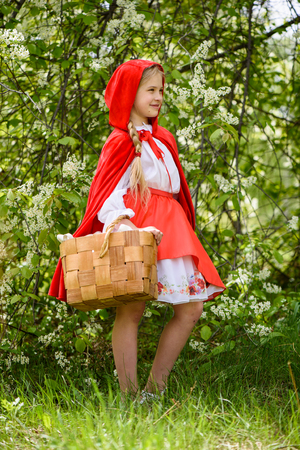 Smiling blond girl posing in a dress of little red riding hood near green trees 免版税图像