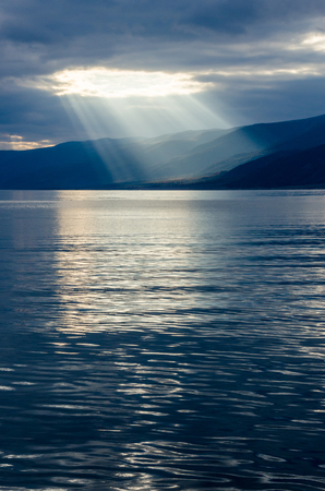Sun shining through thick cloudy sky, silver lining, lake Baikal Imagens