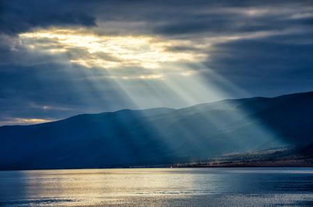 Sun shining through thick cloudy sky, silver lining, lake Baikal 免版税图像