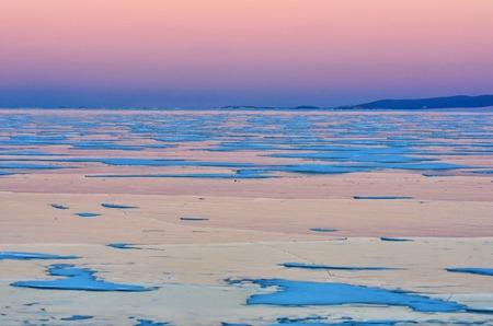 Blue ice of Baikal lake under pink sunset sky and mountain