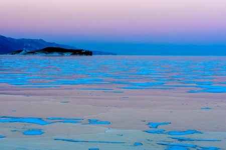 Blue ice of Baikal lake under pink sunset sky and mountain