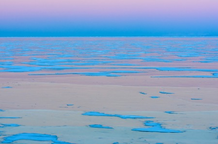 Blue ice of Baikal lake under pink sunset sky. Background