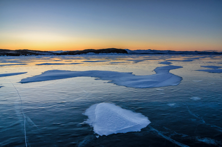 View of beautiful drawings on ice from cracks and bubbles of deep gas on surface of Baikal lake in winter with mountain, Russia