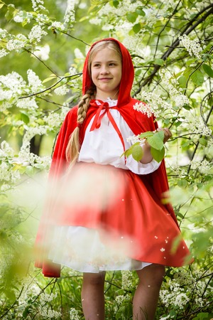 Smiling blond girl posing in a dress of little red riding hood near green trees Stock fotó