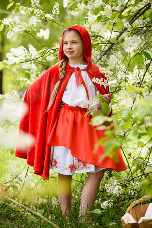 Smiling blond girl posing in a dress of little red riding hood near green trees 写真素材