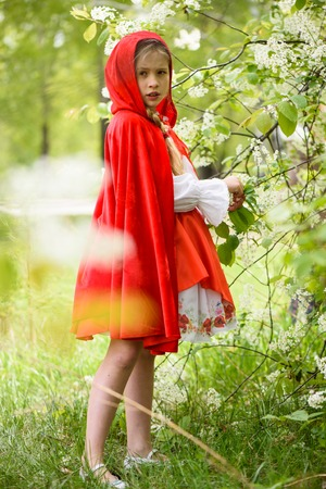 Smiling blond girl posing in a dress of little red riding hood near green trees Archivio Fotografico