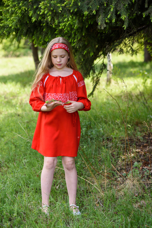 Cute blond young girl posing in a russian traditional red dress near fir tree