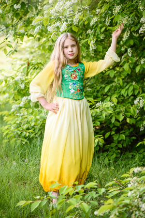 Blond young girl posing in a yellow green dress near birch trees